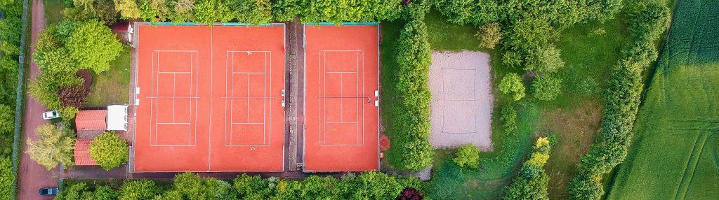 Blick von oben auf die Anlage des TC Harxheim mit drei Tennisplätzen und einem Beachfeld. Zwei Tennisspieler fangen an zu spielen.